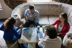 Fondateurs de la réunion d'affaires de démarrage sur le vieux sofa de grand-mamans Photographie stock libre de droits