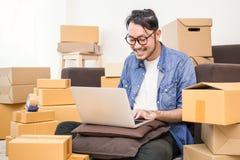 Fondi sulla PMI dell'imprenditore di piccola impresa o freelance uomo asiatico che lavora con la scatola fotografia stock