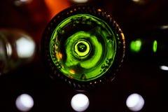Fondi verdi delle bottiglie di vino illuminate da luce intensa Fotografia Stock