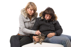 Fondling the cat. Two girl stroking the cat who looks a bit unwilling Stock Images