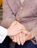 Fondness. Young doctor holds old man's hand Stock Image