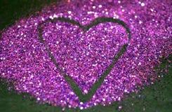 Fondo abstracto borroso con el corazón del brillo púrpura en superficie negra Imagen de archivo libre de regalías
