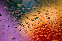 Fondo abstracto colorido de gotas púrpuras, azules, rojas y anaranjadas del agua fotos de archivo libres de regalías