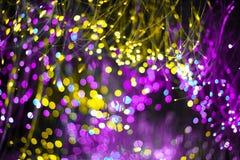 Fondo abstracto con el neón púrpura de la textura del bokeh de la fantasía y el color de oro Fondo de moda de la Navidad imagen de archivo
