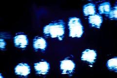 Fondo abstracto con puntos culminantes azules en una superficie oscura del agua foto de archivo libre de regalías