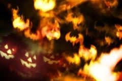 Fondo abstracto de Halloween, caras asustadizas y palos del fuego Imagen de archivo libre de regalías