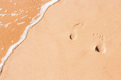 Fondo abstracto de la arena con las pistas de pies Foto de archivo
