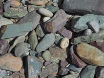Fondo abstracto de las piedras del río de la forma angular y redondeada, verdoso y de Borgoña en color Imagen de archivo