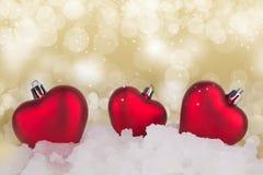 Fondo abstracto del oro de la Navidad con los corazones rojos Fotografía de archivo