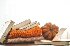 Fondo acogedor del otoño, calabaza decorativa, flores secadas, libros, suéteres calientes, espacio para el texto, leyendo en el d fotografía de archivo