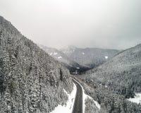Fondo aereo della strada di montagna nella neve di inverno Immagine Stock