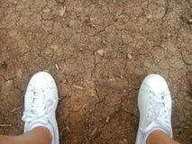 Fondo agrietado sucio del suelo con las zapatillas de deporte Foto de archivo