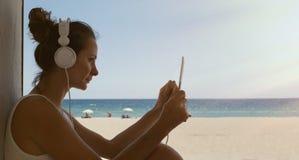 Fondo al aire libre hermoso de la playa de los auriculares de la tableta del concierto de la música de la mujer joven del retrato Imágenes de archivo libres de regalías
