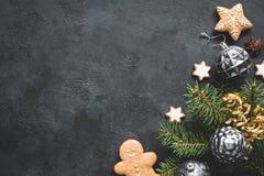 Fondo alla moda di Natale con i giocattoli d'annata, l'albero di abete ed i biscotti su fondo di pietra nero fotografie stock
