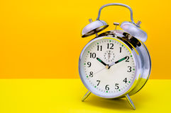 Fondo anaranjado y amarillo del reloj de alarma - Foto de archivo libre de regalías