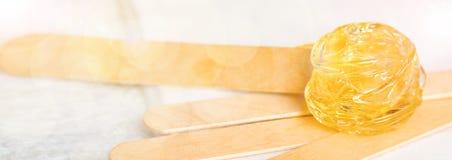 Fondo ancho adicional de la bandera con goma del azúcar o encerar la miel para la eliminación del pelo y los palillos de madera foto de archivo