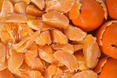 Fondo arancio di progettazione dalle arance fresche pure dei lobuli, a destra alcune arance in buccia incrinata spessa Fotografia Stock Libera da Diritti