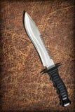 Fondo arrugado resistido Bowie Knife Set On Old del Grunge de Vignetted del zurriago de Sawback Brown de la supervivencia de la c Fotos de archivo