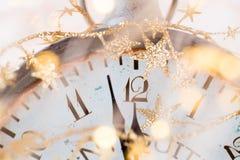 Fondo astratto con i fuochi d'artificio e l'orologio vicino alla mezzanotte Natale e buoni anni di fondo di vigilia immagine stock
