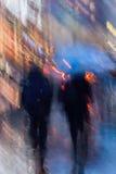 Fondo astratto della gente che affretta giù la via nella sera piovosa, finestre della città del negozio Mosso intenzionale Fotografia Stock Libera da Diritti