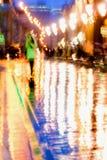 Fondo astratto della ragazza in cappotto verde intenso Riflessioni luminose delle lampade di via nel moto intenzionale dell'asfal Immagine Stock