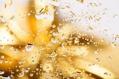 Fondo astratto dorato con le gocce di acqua Fotografia Stock