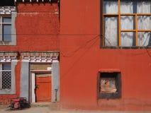 Fondo astratto luminoso di struttura di lerciume dalla costruzione di colore rosso della parete con le finestre d'annata a strisc Immagini Stock Libere da Diritti