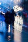Fondo astratto nei toni del blu del naturale La gente che cammina giù la via della città nella sera piovosa Moto intenzionale Immagini Stock Libere da Diritti