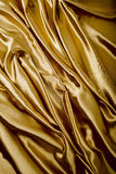 Fondo astratto, tessuto dell'oro dei drappi. Fotografie Stock Libere da Diritti