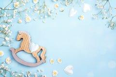 Fondo azul con el mini flowe del juguete y del gypsophila del caballo mecedora Fotografía de archivo