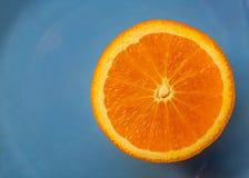 Fondo azul con la fruta cítrica de la fruta una mandarina anaranjada o media Imagen macra y primer, concepto para la comida sana fotos de archivo libres de regalías