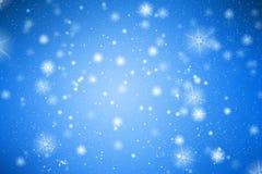 Fondo azul con los copos de nieve blancos imagen de archivo