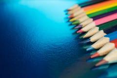 Fondo azul con los lápices coloreados Imagenes de archivo