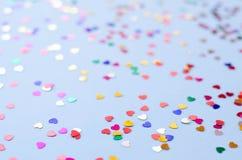 Fondo azul con los pequeños corazones multicolores foto de archivo