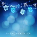Fondo azul de Anukkah con la cadena de luz y de dreidels Foto de archivo libre de regalías