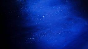 Fondo azul de la partícula que brilla Polvo azul del universo con las estrellas en fondo negro Extracto del movimiento de partícu metrajes