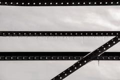 Fondo bajo casi abstracto industrial de la saturación de las tiras de metal rígidas con los agujeros contra el cielo gris con el  foto de archivo libre de regalías