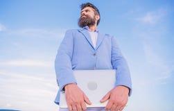 Fondo barbudo del cielo azul del ordenador port?til del control del encargado del inconformista del hombre Empresario moderno del foto de archivo