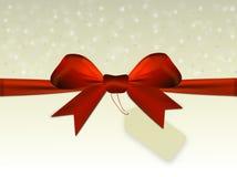 Fondo beige brillante con el arco rojo con la etiqueta Fotografía de archivo libre de regalías