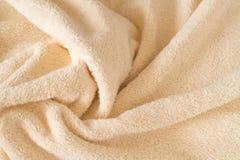 Fondo beige lanuginoso dell'asciugamano, primo piano Tessuto pastello del bambino delicato con le onde ed i popolare Struttura ar fotografie stock