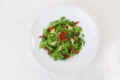 Fondo bianco del piatto circolare superiore del parmigiano dei pomodori secco insalata della rucola isolato Fotografia Stock Libera da Diritti