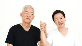 Fondo bianco delle coppie della tenuta della mano di espressione senior asiatica di matrimonio felice insieme immagine stock libera da diritti