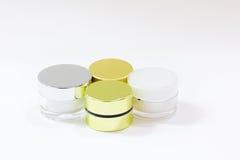 Fondo blanco aislado poner crema de la botella de cristal Imágenes de archivo libres de regalías