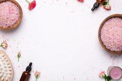 Fondo blanco con la sal de baño, el massager y las botellas de aceite naturales foto de archivo libre de regalías