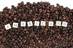 Fondo blanco de granos del texto Y de café del cubo de AMERICANO Foto de archivo