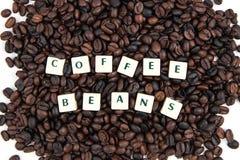 Fondo blanco de granos del texto Y de café del cubo de los GRANOS de CAFÉ Foto de archivo libre de regalías