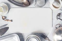 Fondo blanco de la cocina - tabla de cortar adornada con el cookware fotos de archivo