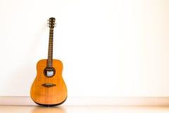 Fondo blanco de la pared del aislante de la guitarra acústica Imagenes de archivo