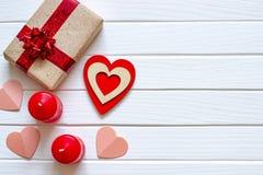Fondo blanco de madera con los corazones, los regalos y las velas rojos El concepto de Valentine Day Visión superior imagenes de archivo