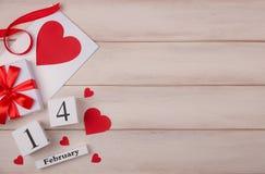 Fondo blanco de madera con los corazones rojos, los regalos, el sobre del amor y el calendario de bloque de madera El concepto de fotos de archivo libres de regalías